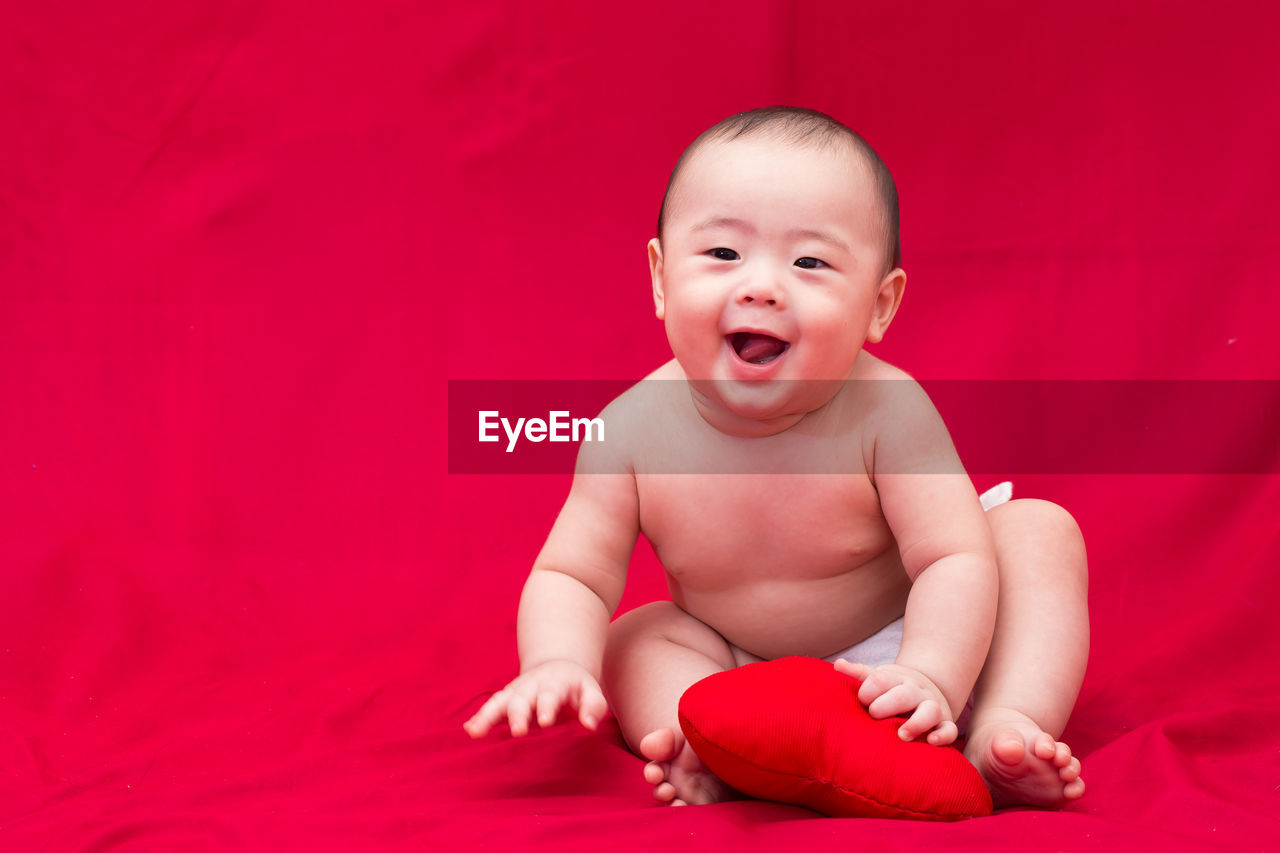 Portrait of happy baby with heart shape sitting on red textile