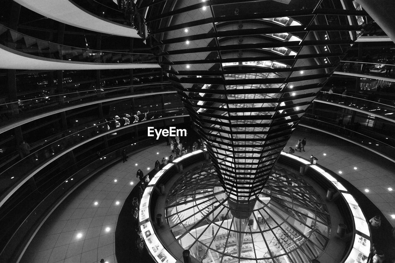 architecture, built structure, indoors, spiral, illuminated, steps and staircases, staircase, pattern, modern, high angle view, railing, real people, building, curve, night, spiral staircase, architectural feature, ceiling