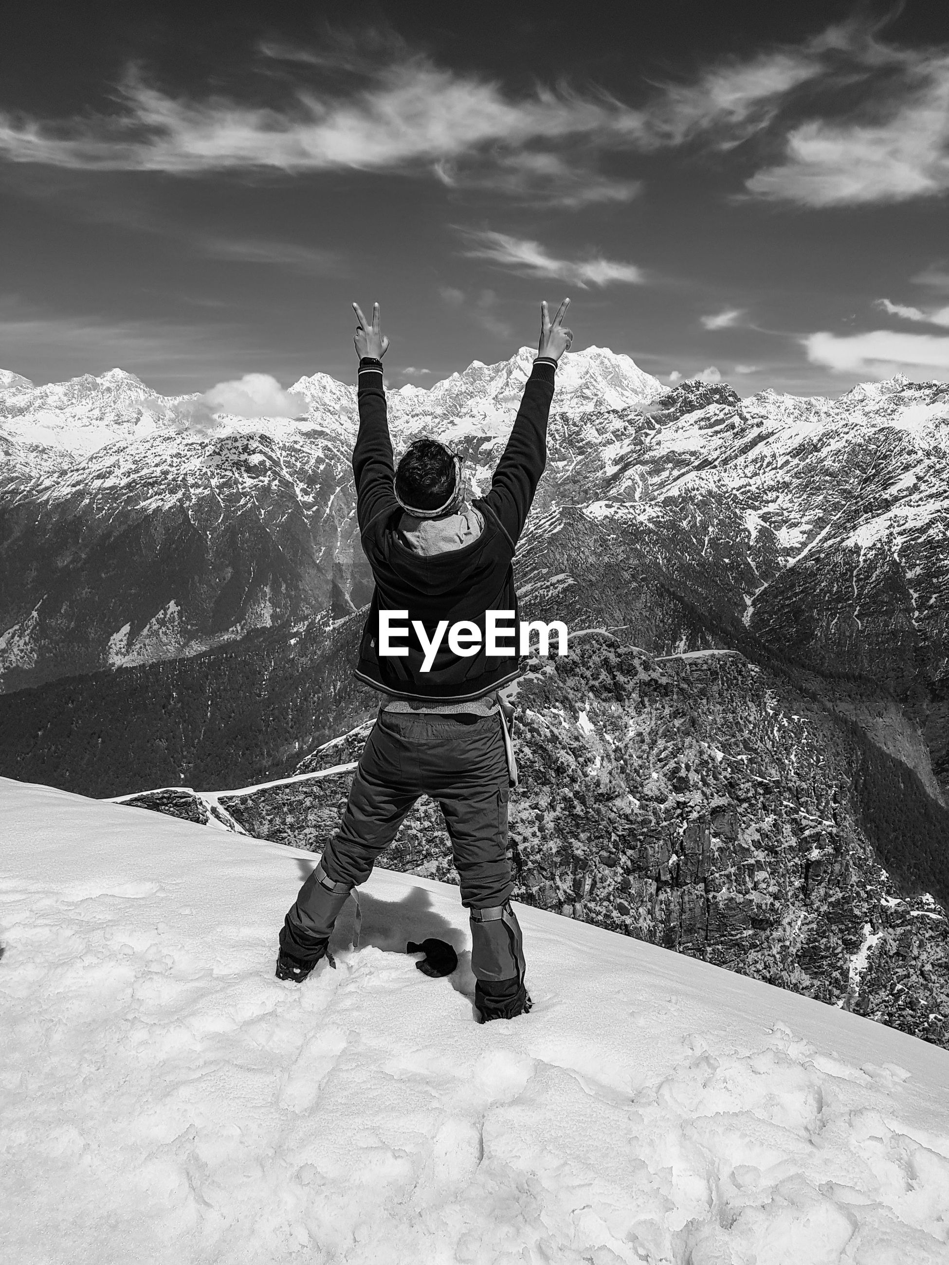 Rear view of man standing with arms raised on snowcapped mountain against sky