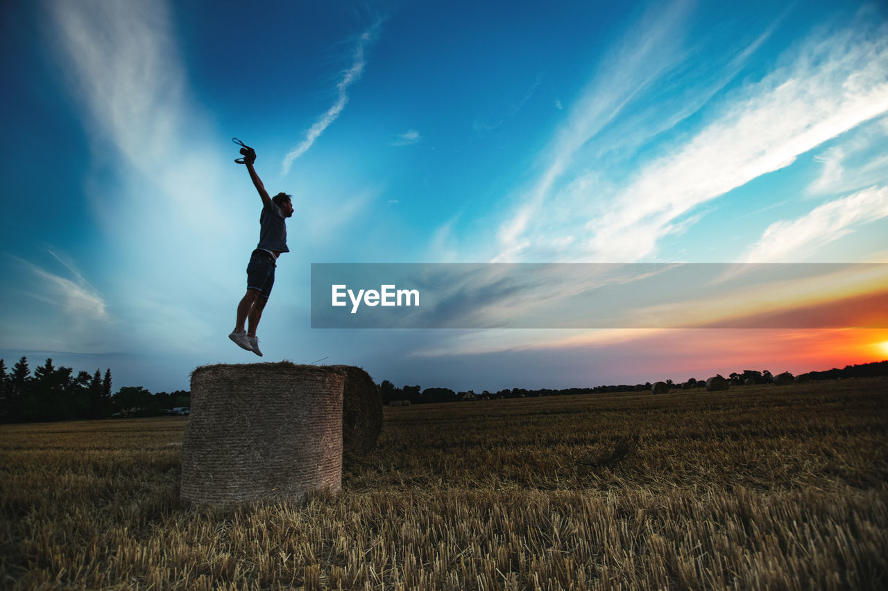 Man Jumping On Hay Bale Against Dramatic Sky During Sunset