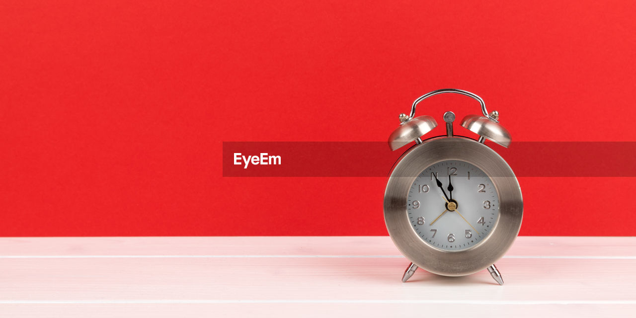 Close-up of clock on table against red background