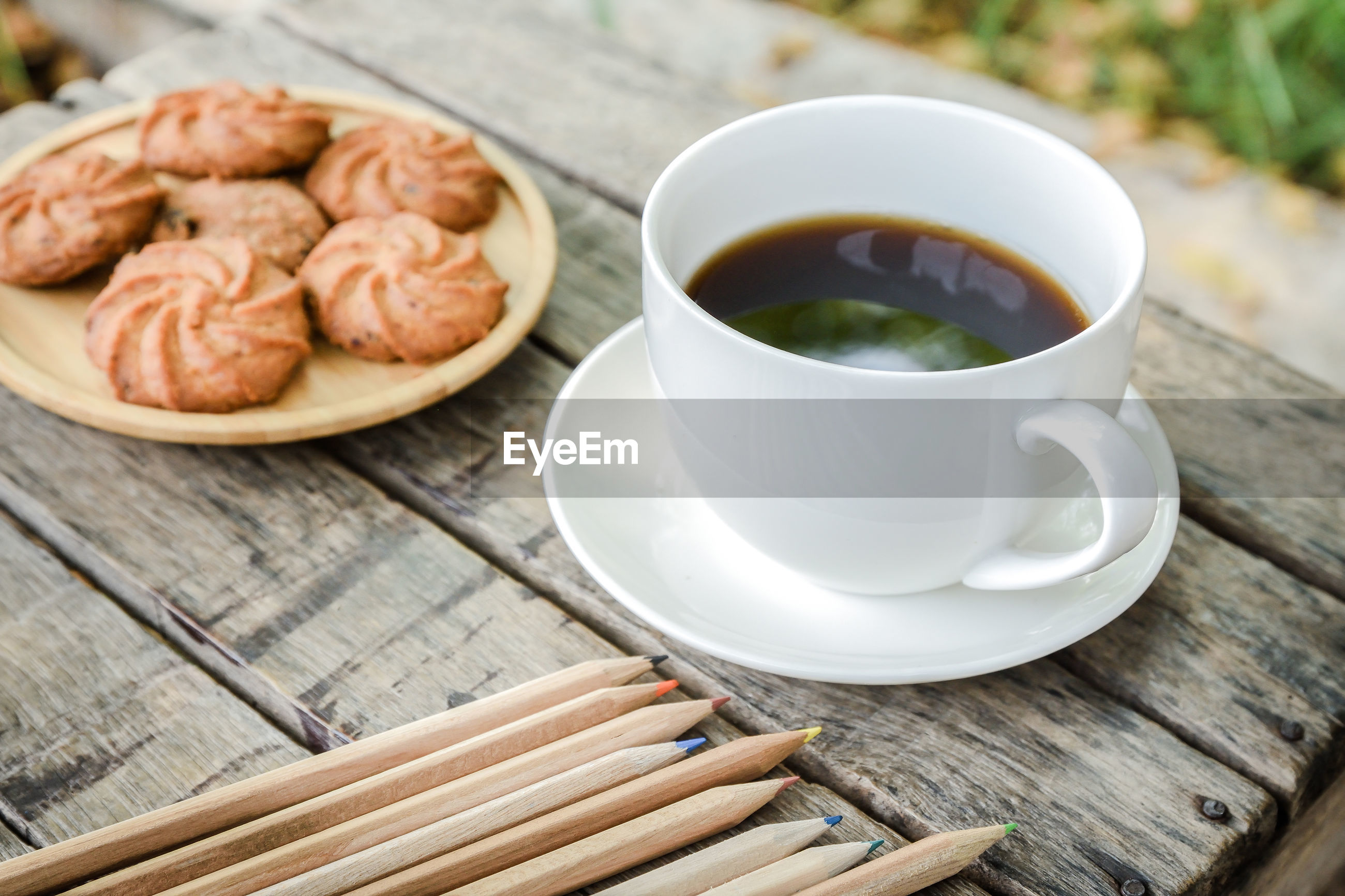 Close-up of coffee and cookies with pencils on table