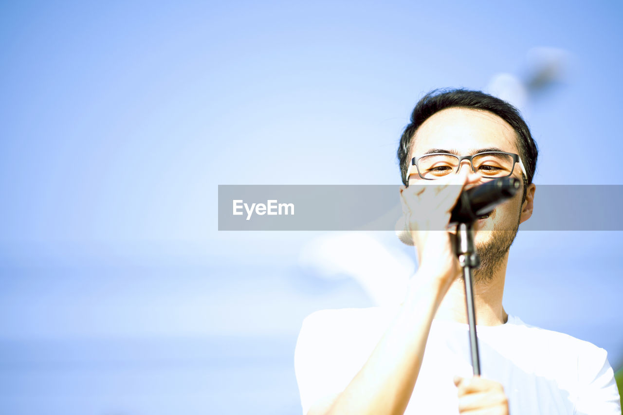 Close-Up Of Man Singing While Standing Against Blue Sky