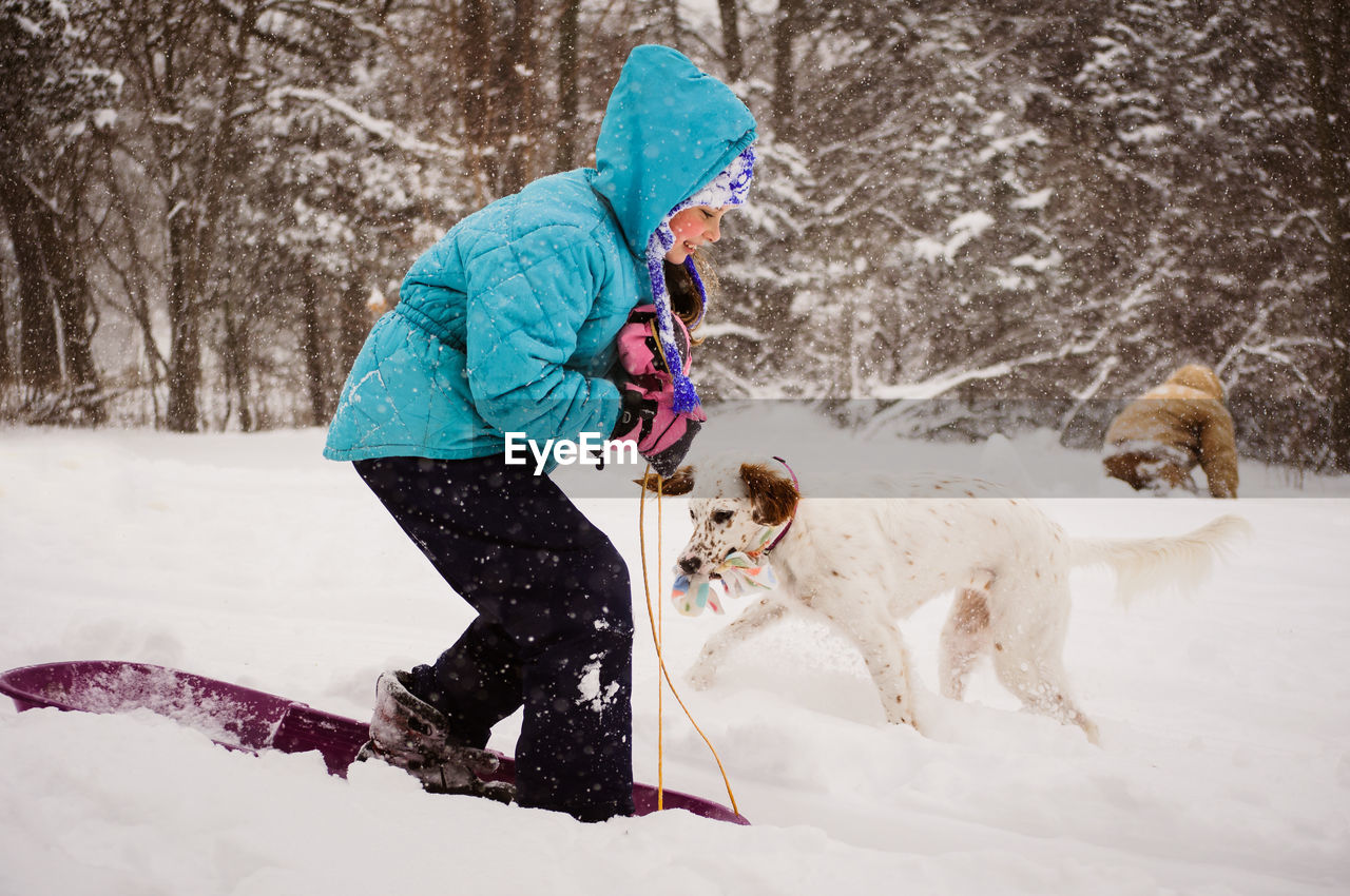 Side view of girl sledding by dog on snow covered field
