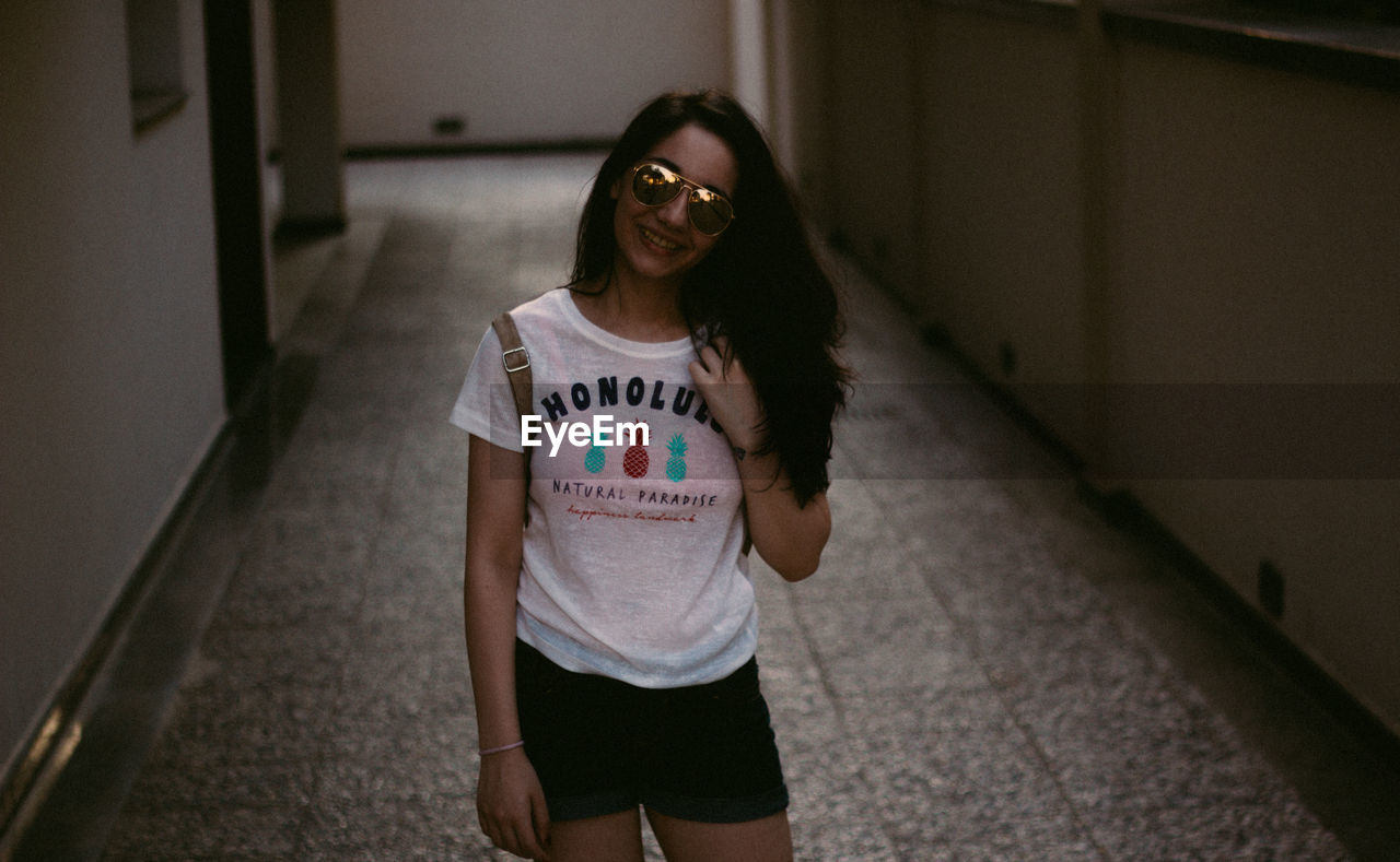 real people, front view, young adult, one person, young women, sunglasses, lifestyles, leisure activity, three quarter length, looking at camera, casual clothing, long hair, happiness, portrait, smiling, indoors, standing, full length, architecture, day