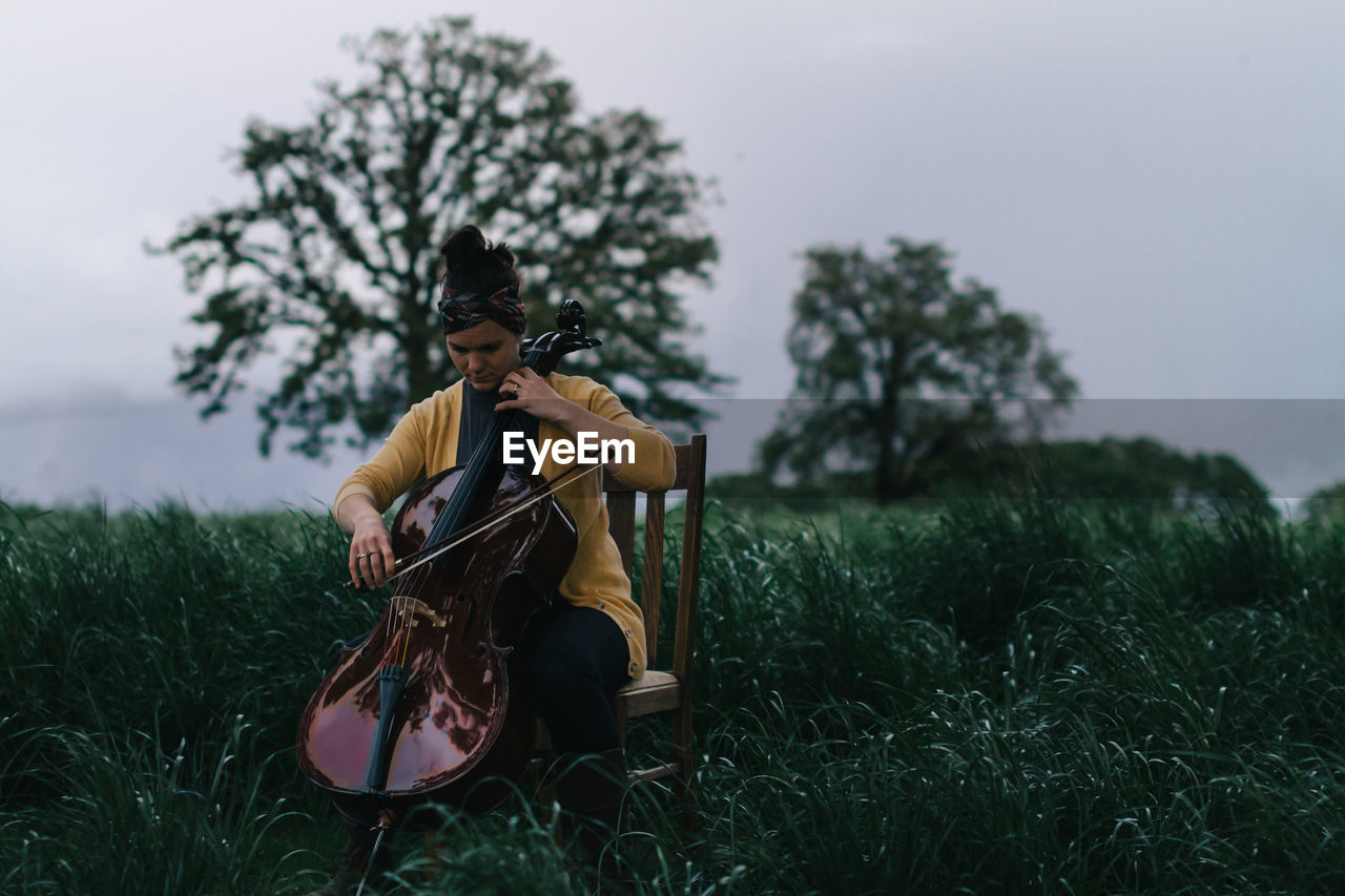 Young Woman Playing Cello On Field Against Sky