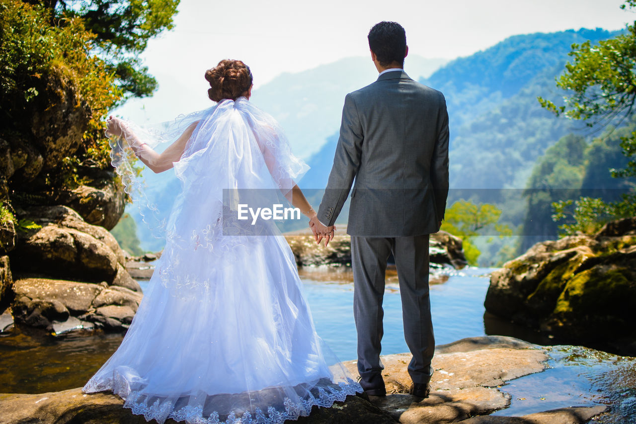 rear view, two people, love, bride, couple - relationship, adult, real people, newlywed, men, wedding, women, togetherness, married, celebration, positive emotion, nature, event, wedding dress, bonding, full length, outdoors