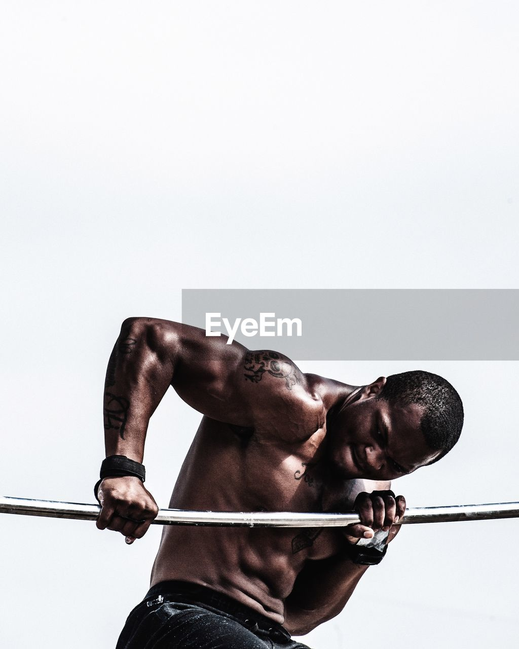 Shirtless young man lifting weights while standing against white background