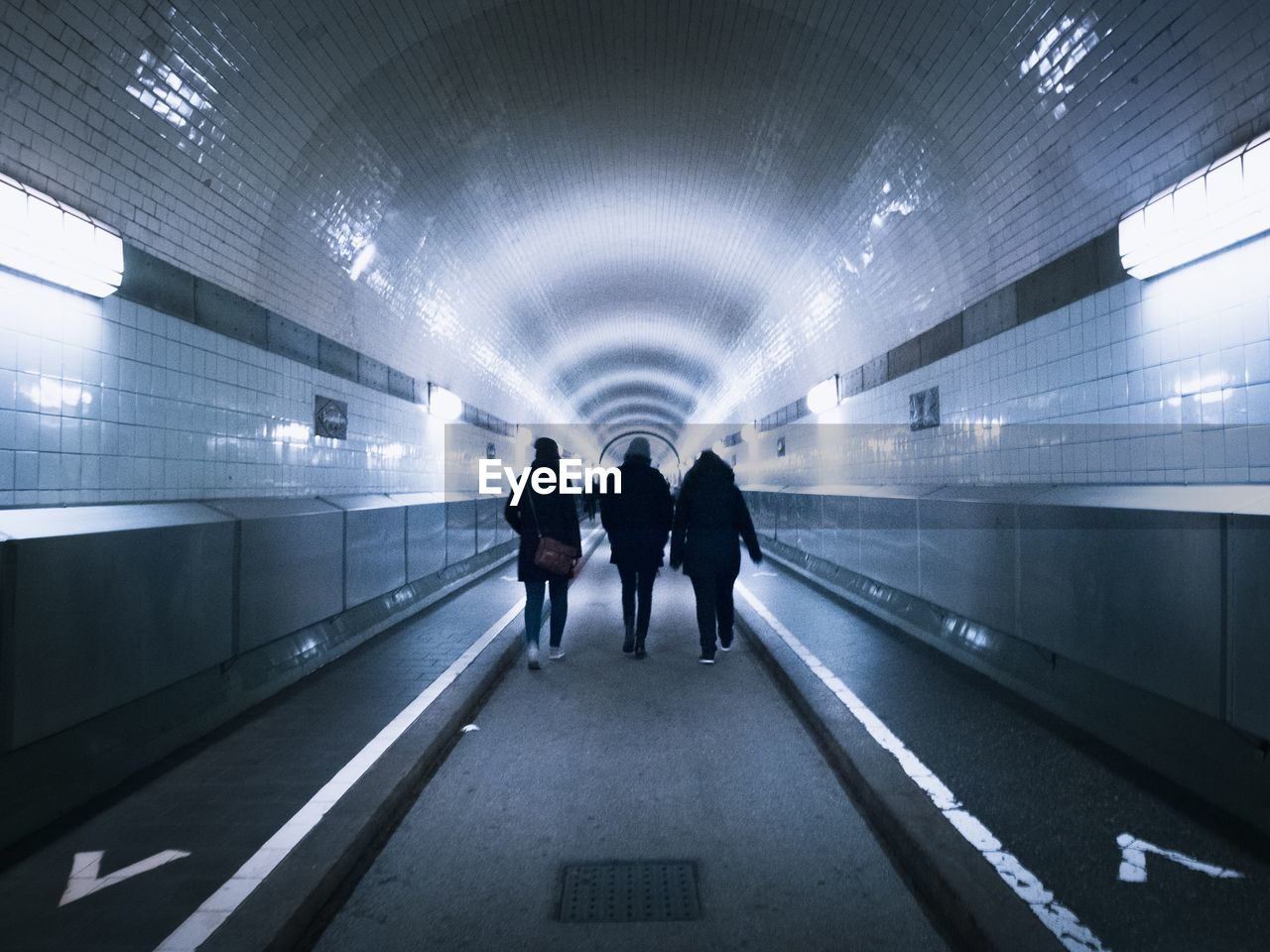 Rear view of three people walking in tunnel