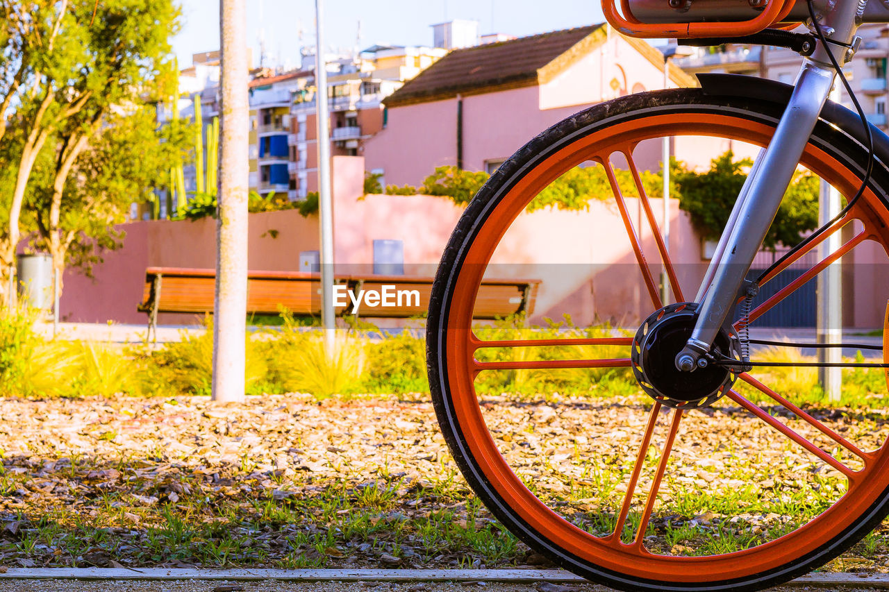 transportation, land vehicle, wheel, focus on foreground, mode of transportation, day, bicycle, no people, nature, close-up, stationary, outdoors, metal, architecture, built structure, building exterior, field, sunlight, city, yellow, tire, spoke