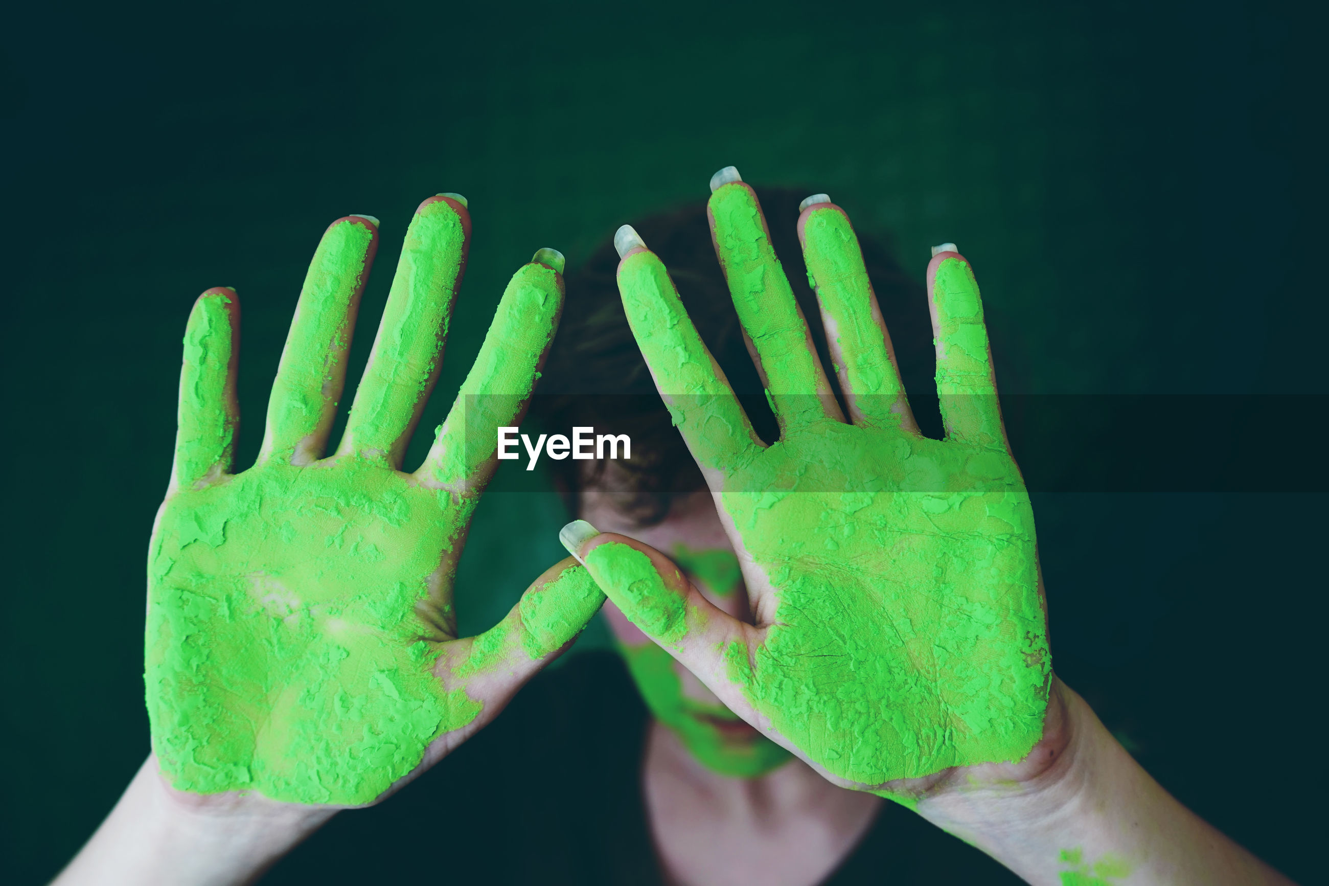 Close-up of woman gesturing with green hands
