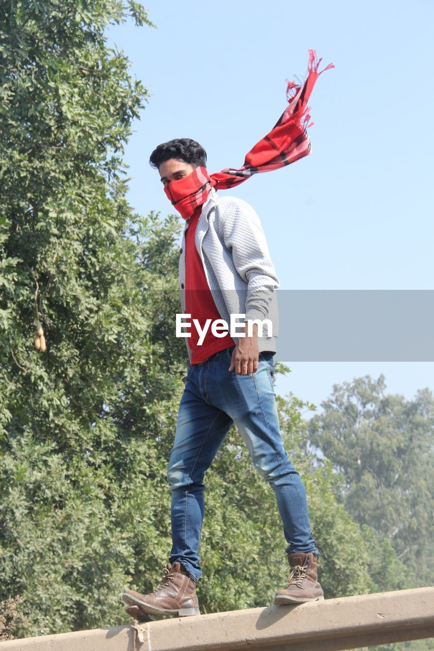 Low angle portrait of man covering face with scarf while standing against trees