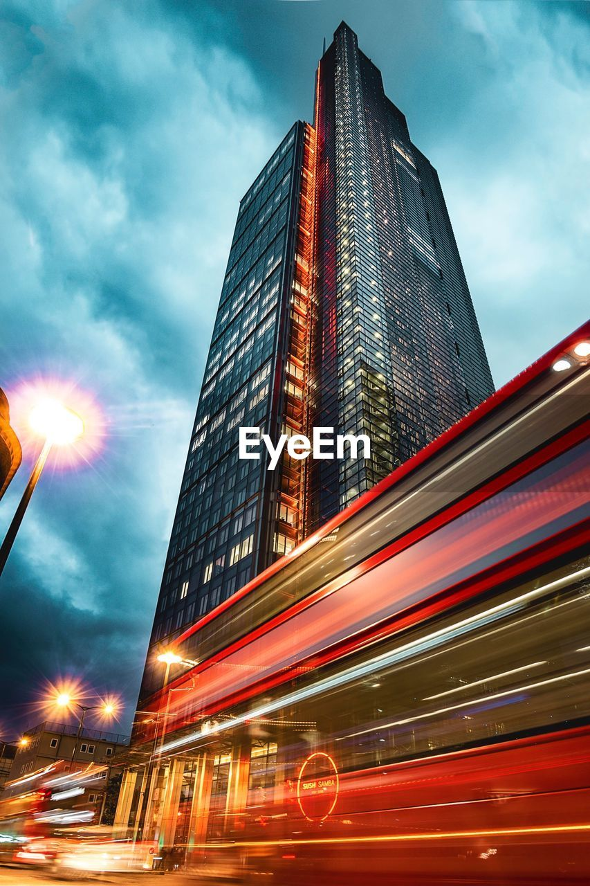 architecture, building exterior, city, sky, illuminated, built structure, skyscraper, cloud - sky, outdoors, speed, modern, low angle view, blurred motion, city life, transportation, no people, motion, travel destinations, night