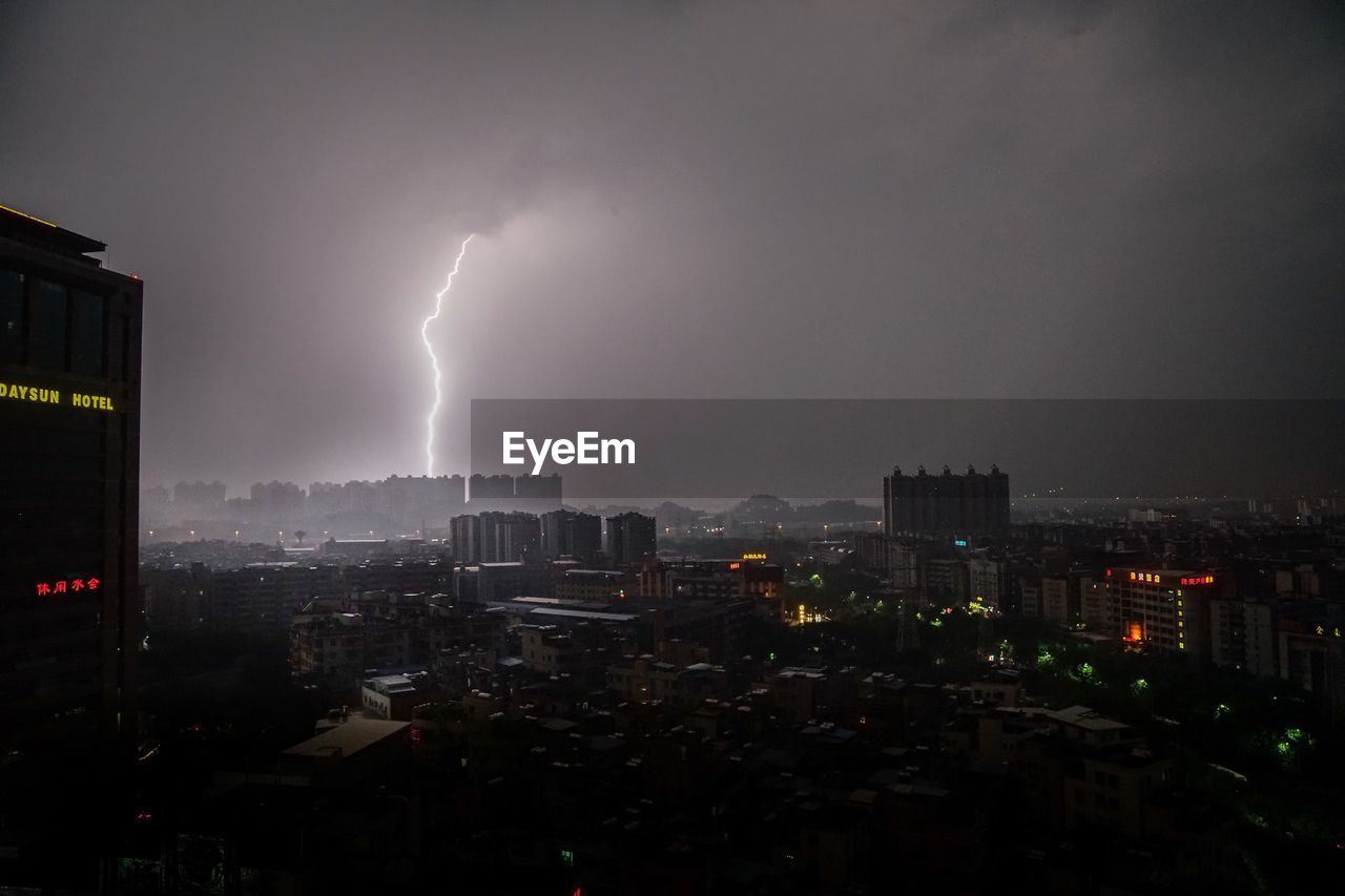 Buildings Against Lightning In Cloudy Sky At Night