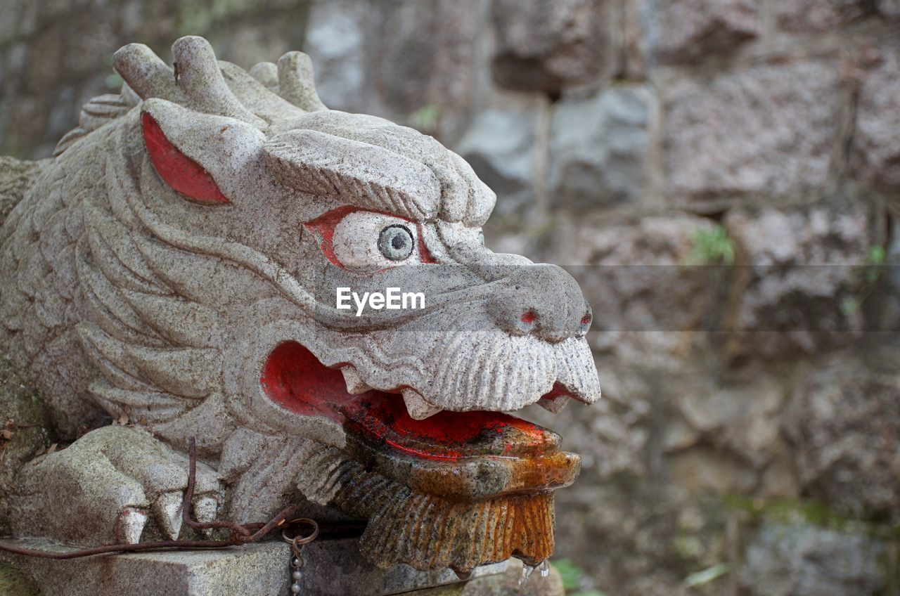 animal representation, representation, art and craft, sculpture, statue, focus on foreground, close-up, no people, day, craft, creativity, animal, dragon, animal themes, outdoors, carving - craft product, solid, stone material, animal head, mouth open
