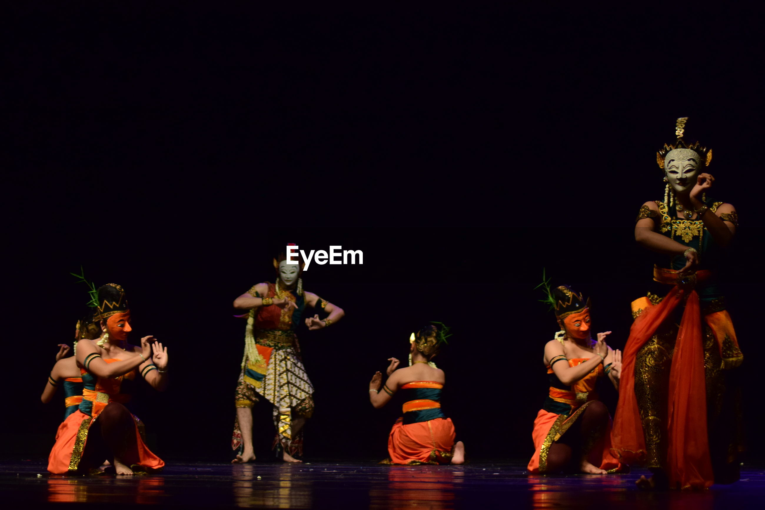 Dancers wearing traditional clothing while dancing against black background