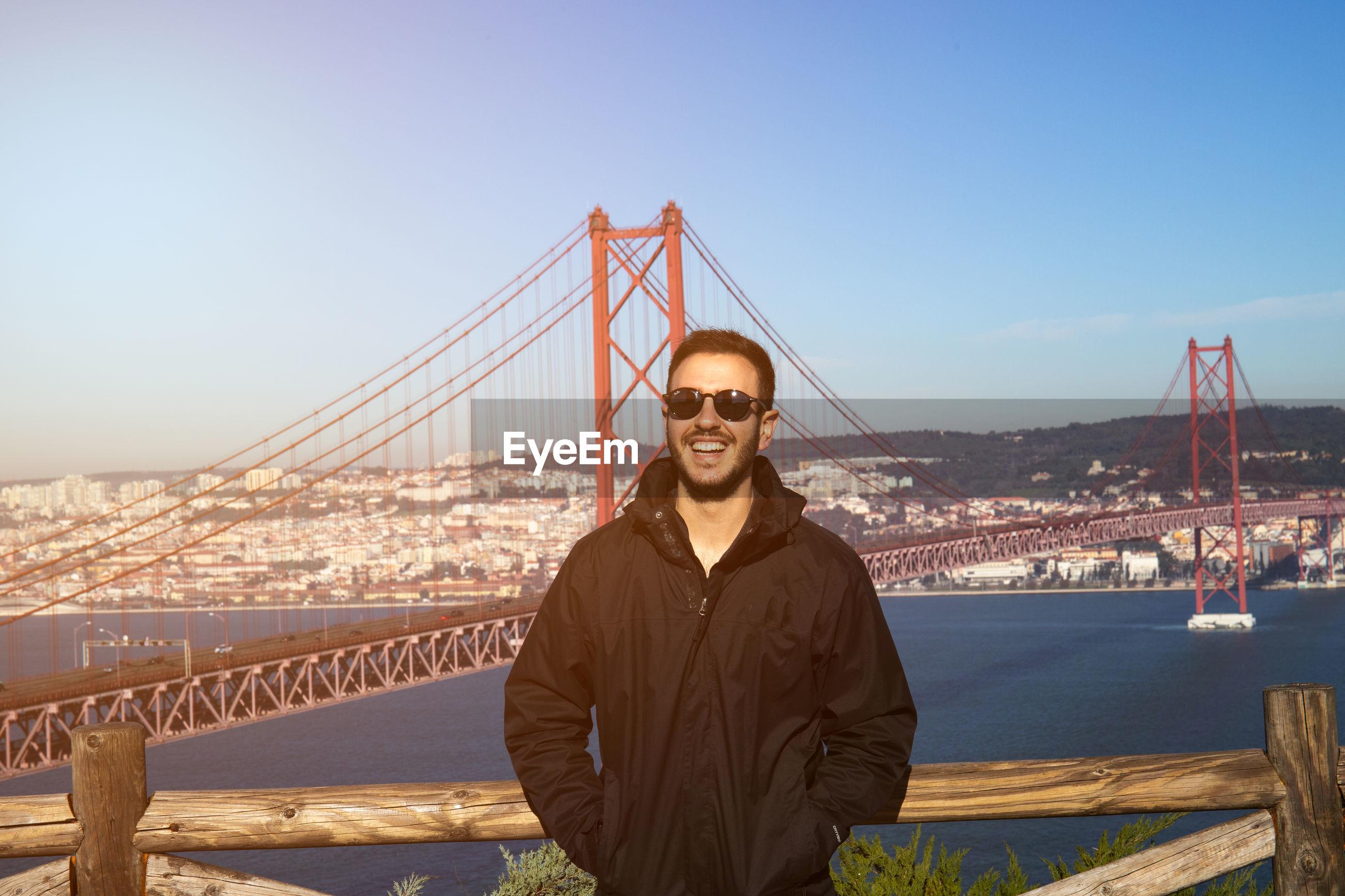 Happy mid adult man wearing sunglasses standing against golden gate bridge