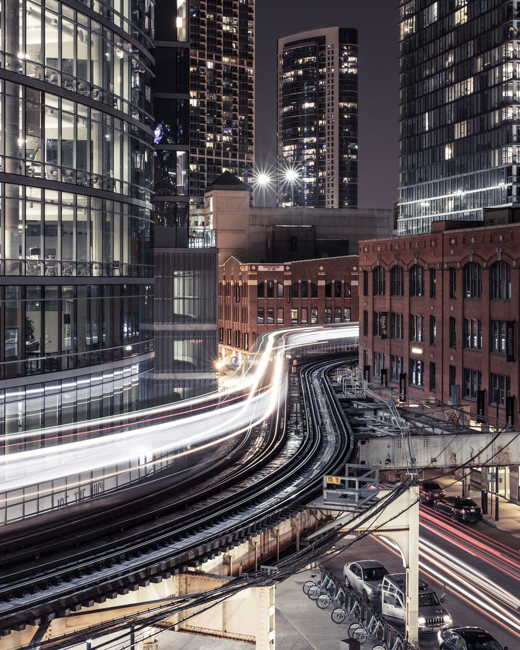 architecture, building exterior, illuminated, built structure, city, night, motion, transportation, long exposure, light trail, street, speed, road, building, city life, office building exterior, blurred motion, cityscape, traffic, residential district, skyscraper, no people, outdoors, bridge - man made structure, multiple lane highway, modern, financial district