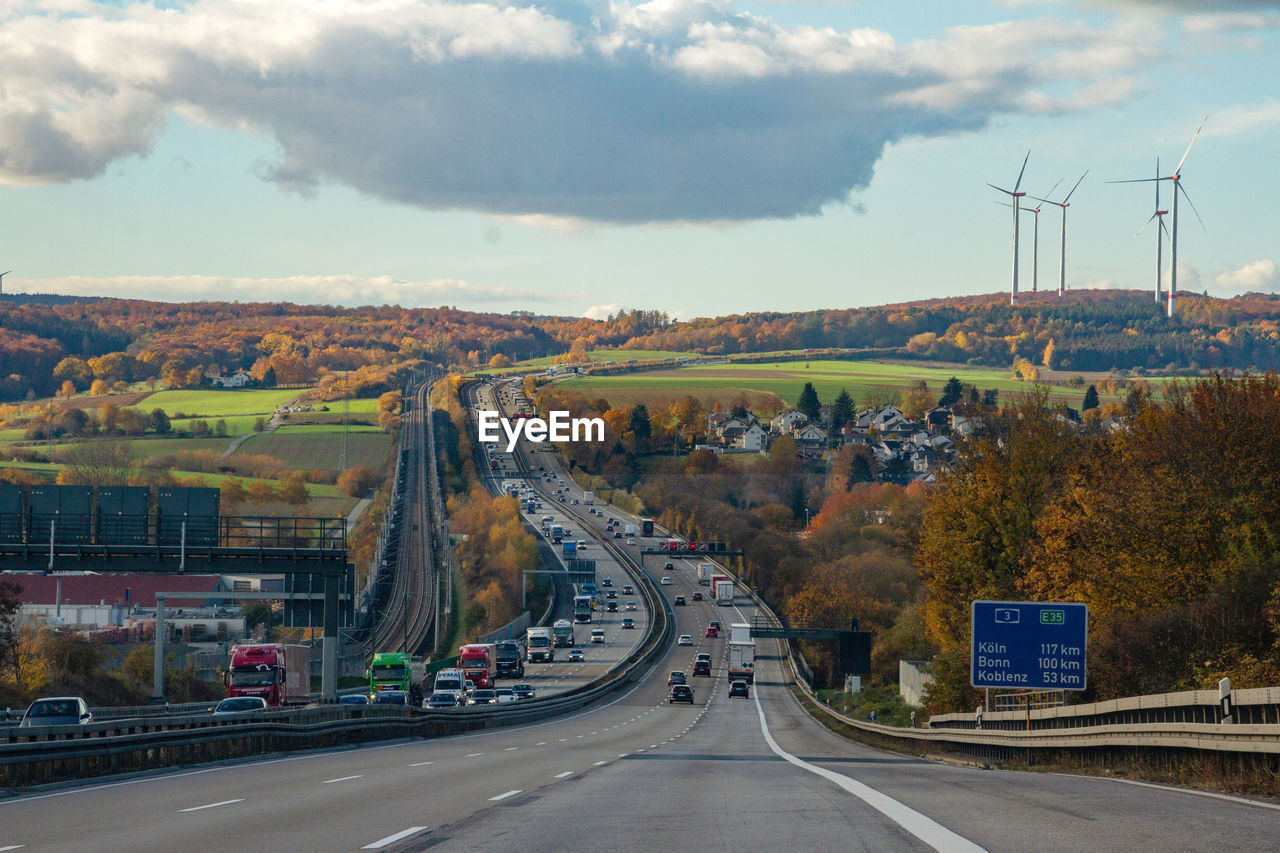 transportation, road, sign, sky, cloud - sky, the way forward, direction, nature, road marking, motor vehicle, mode of transportation, car, marking, symbol, highway, land vehicle, no people, day, connection, environment, outdoors, multiple lane highway, dividing line