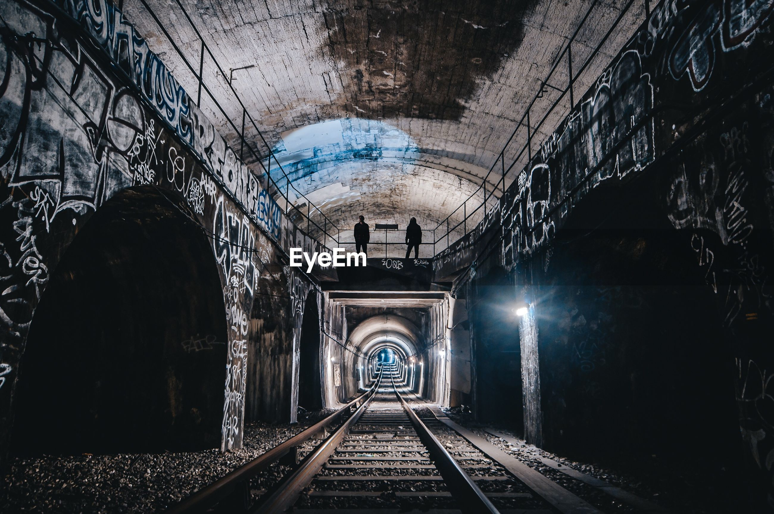 architecture, rail transportation, arch, tunnel, track, the way forward, direction, railroad track, built structure, transportation, indoors, public transportation, no people, diminishing perspective, illuminated, mode of transportation, wall - building feature, abandoned, travel, vanishing point, light at the end of the tunnel, long, ceiling