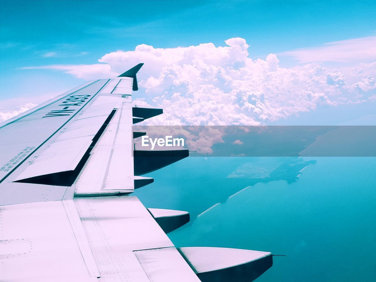 Cropped Image Of Airplane Wing Over Sea Against Cloudy Sky