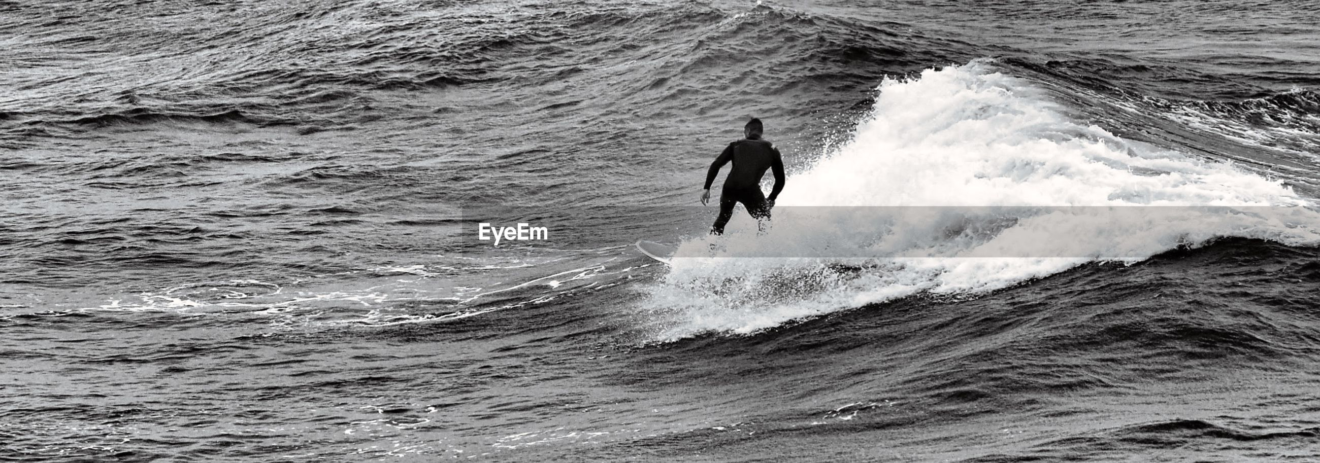 MAN SURFING ON SEA WAVES
