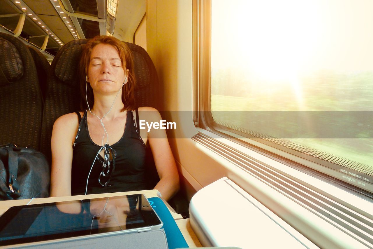 Woman listening music while sitting in train