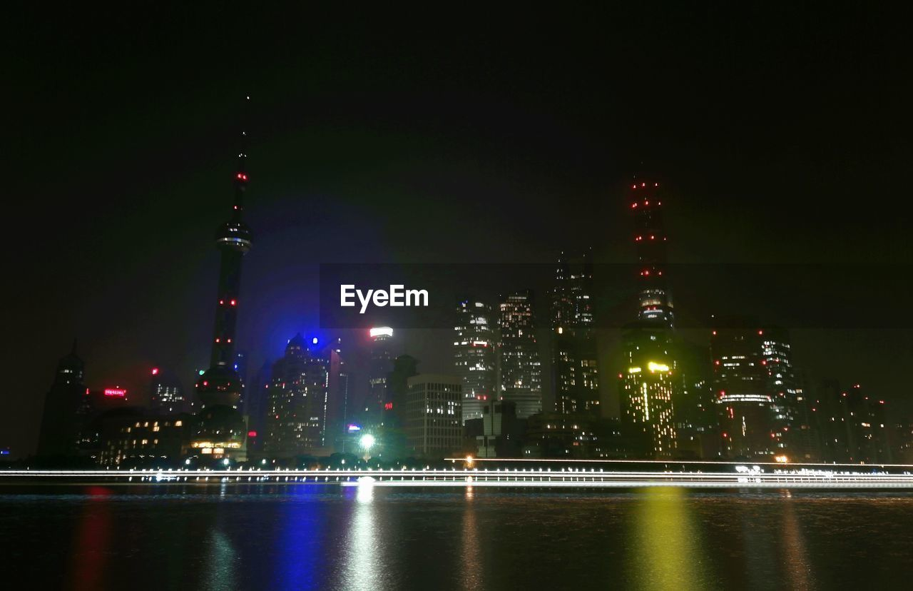 building exterior, night, architecture, illuminated, built structure, city, water, building, tall - high, waterfront, tower, sky, skyscraper, no people, office building exterior, travel destinations, urban skyline, cityscape, modern, spire, outdoors, financial district