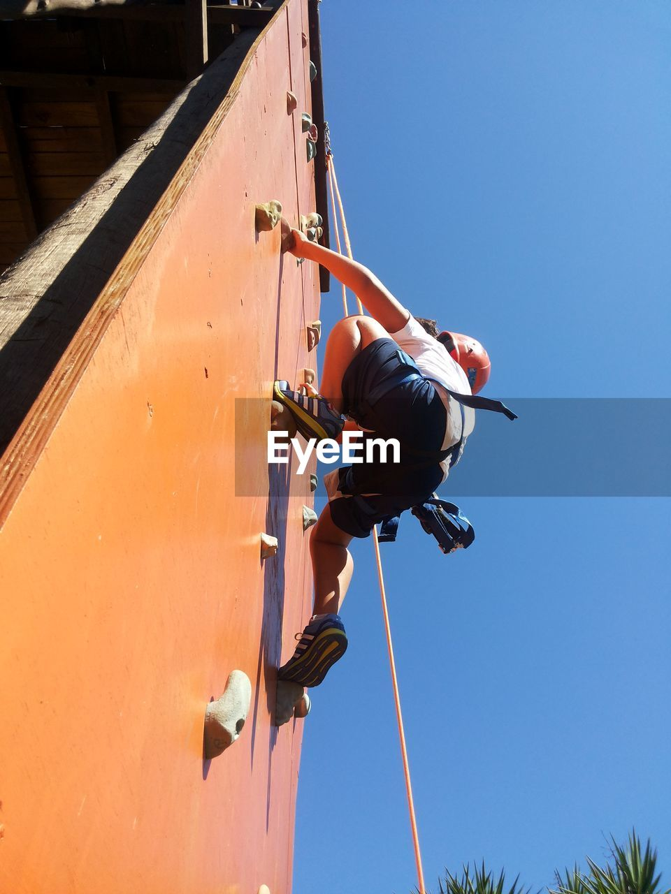 Low angle view of person climbing wall against sky