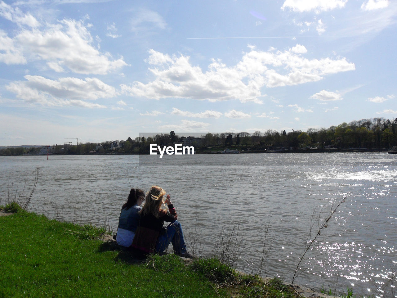 Rear view of friends sitting on grass field by river against sky