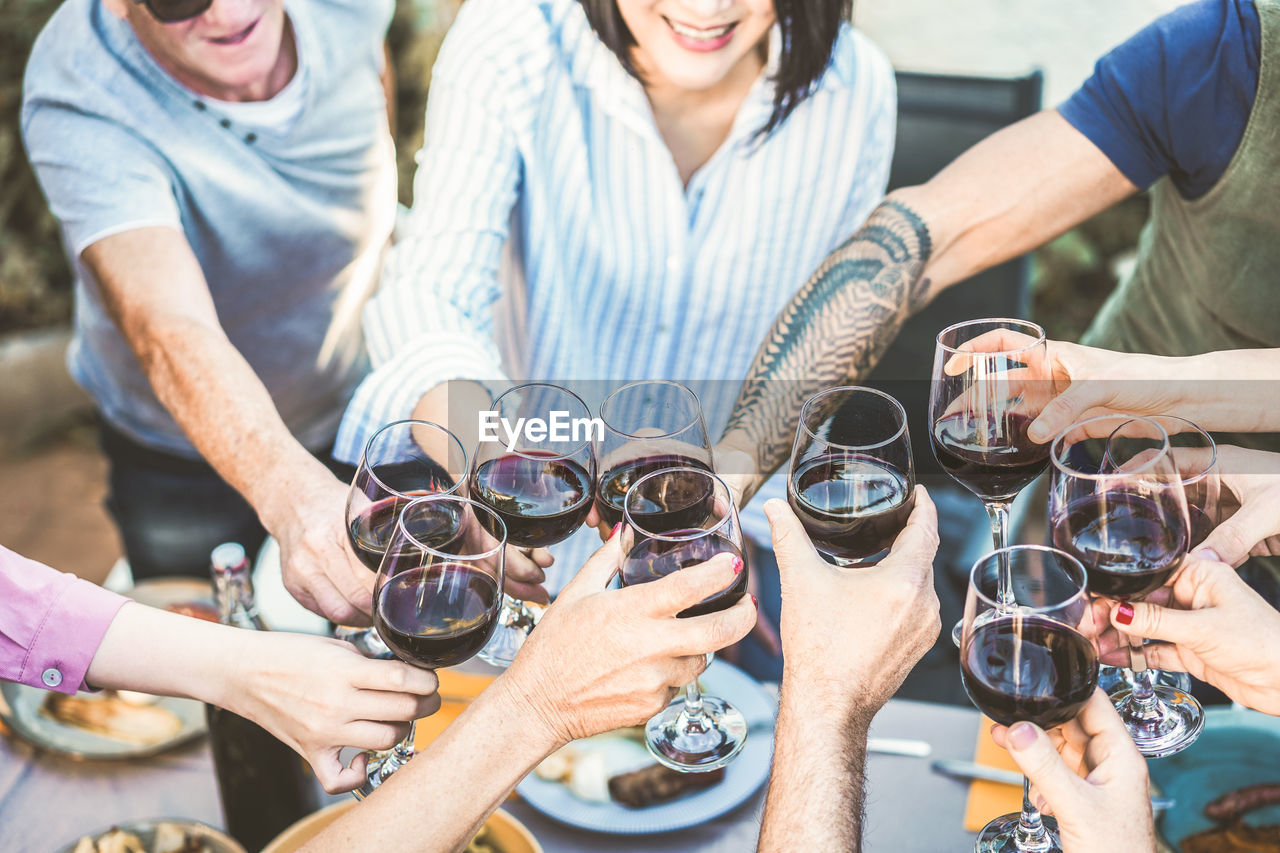 group of people, alcohol, wine, drink, wineglass, friendship, real people, glass, refreshment, human hand, men, smiling, togetherness, women, celebratory toast, adult, red wine, holding, lifestyles, hand, drinking, mature men