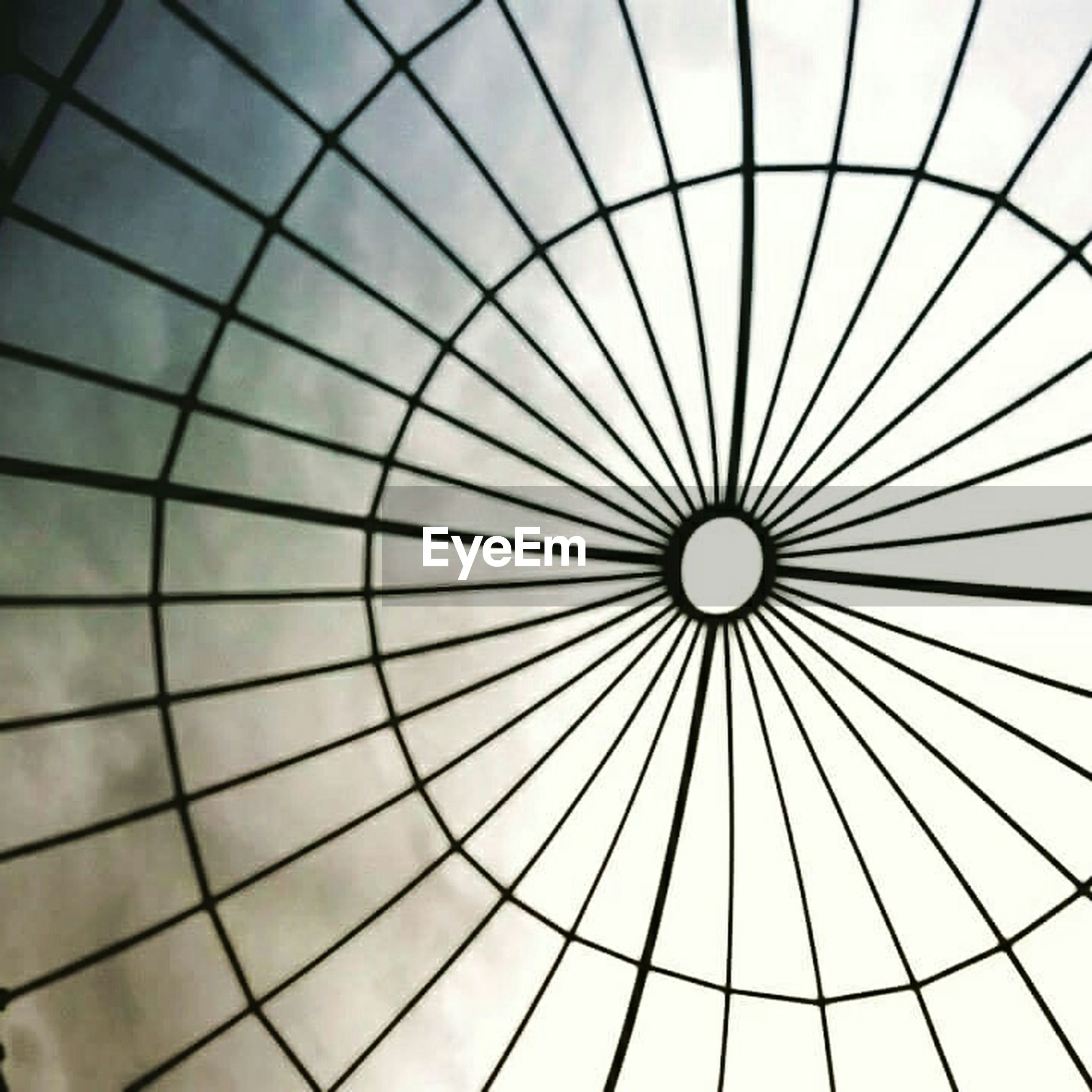 low angle view, ceiling, pattern, architecture, indoors, built structure, design, directly below, geometric shape, modern, full frame, backgrounds, architectural feature, shape, glass - material, skylight, repetition, no people, circle, abstract