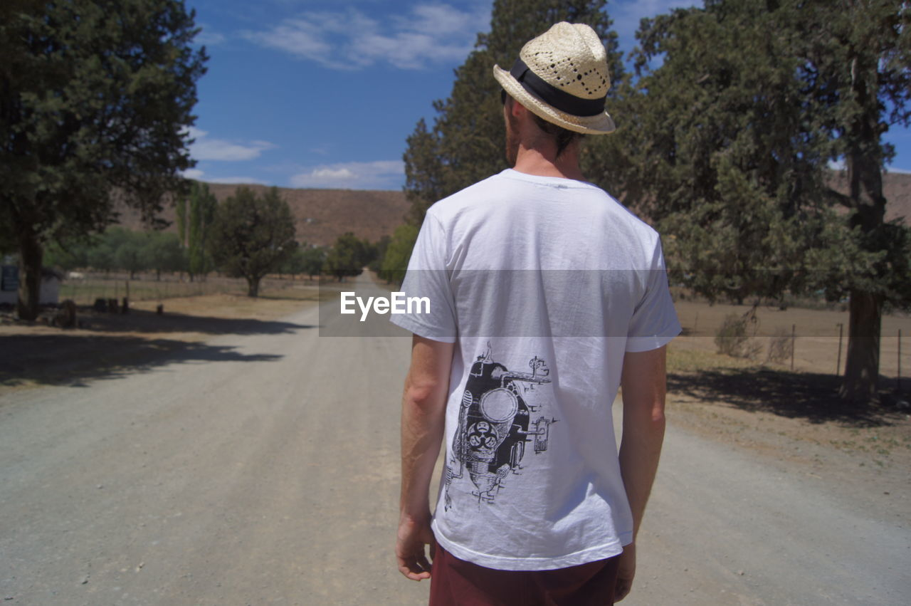 Rear View Of Man Standing On Road During Sunny Day
