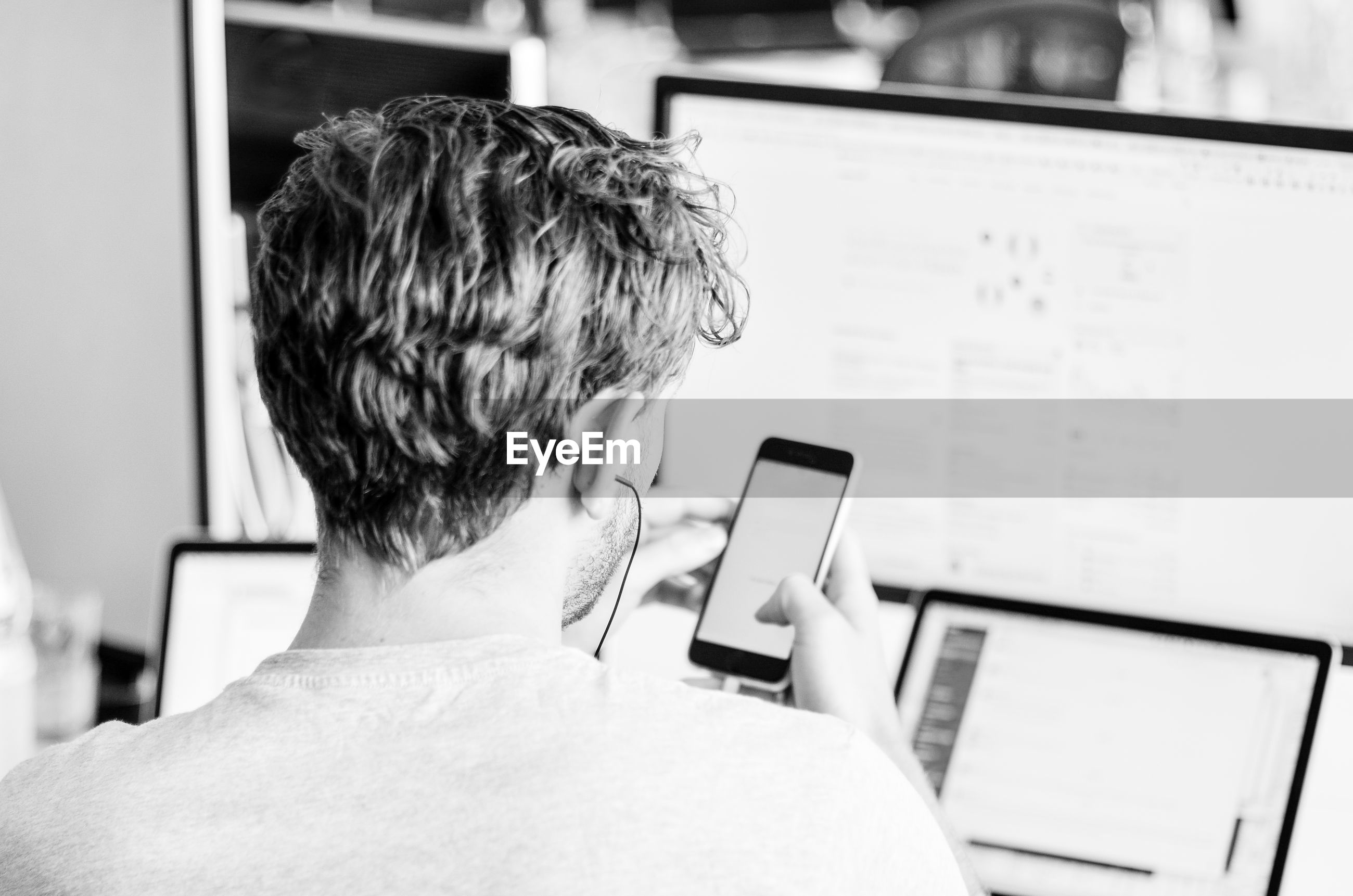 REAR VIEW OF MAN USING MOBILE PHONE IN OFFICE
