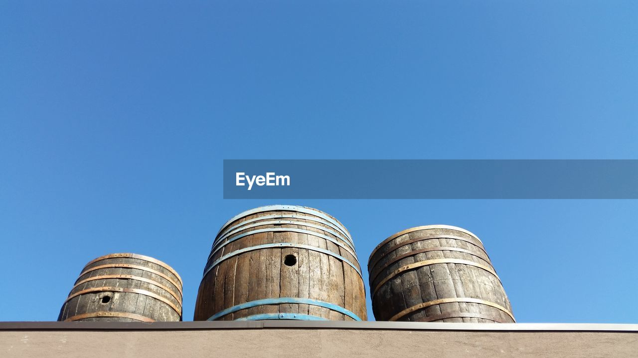 Low Angle View Of Wooden Barrels Against Clear Sky