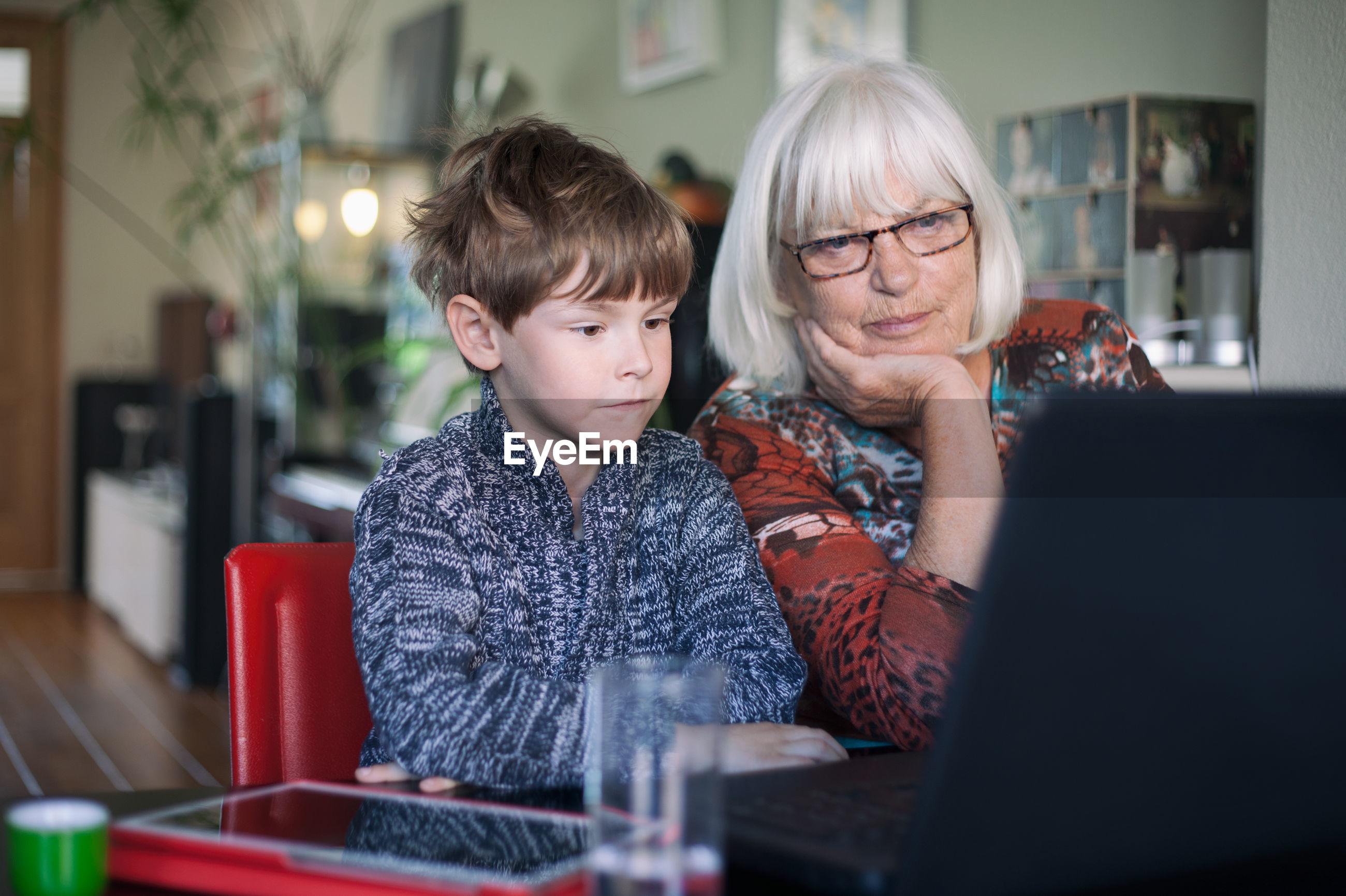 Grandmother and grandson sitting at restaurant