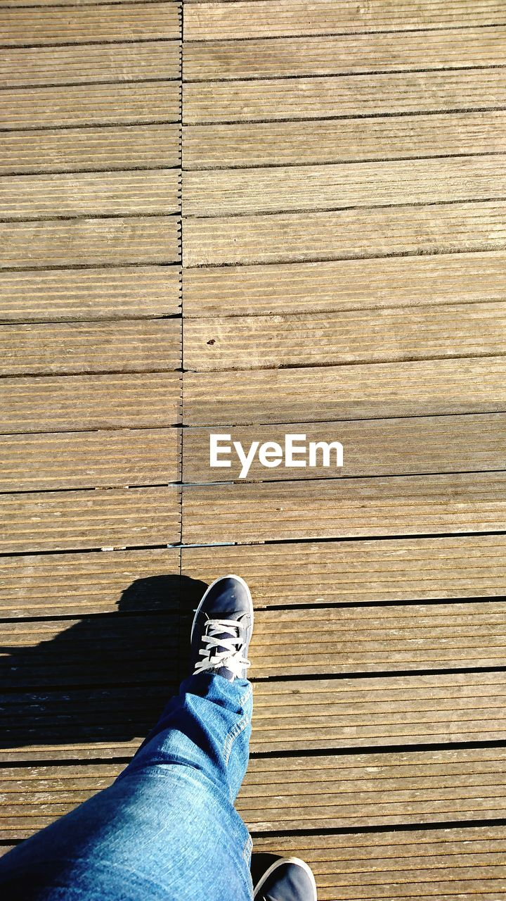Low section of man standing on boardwalk