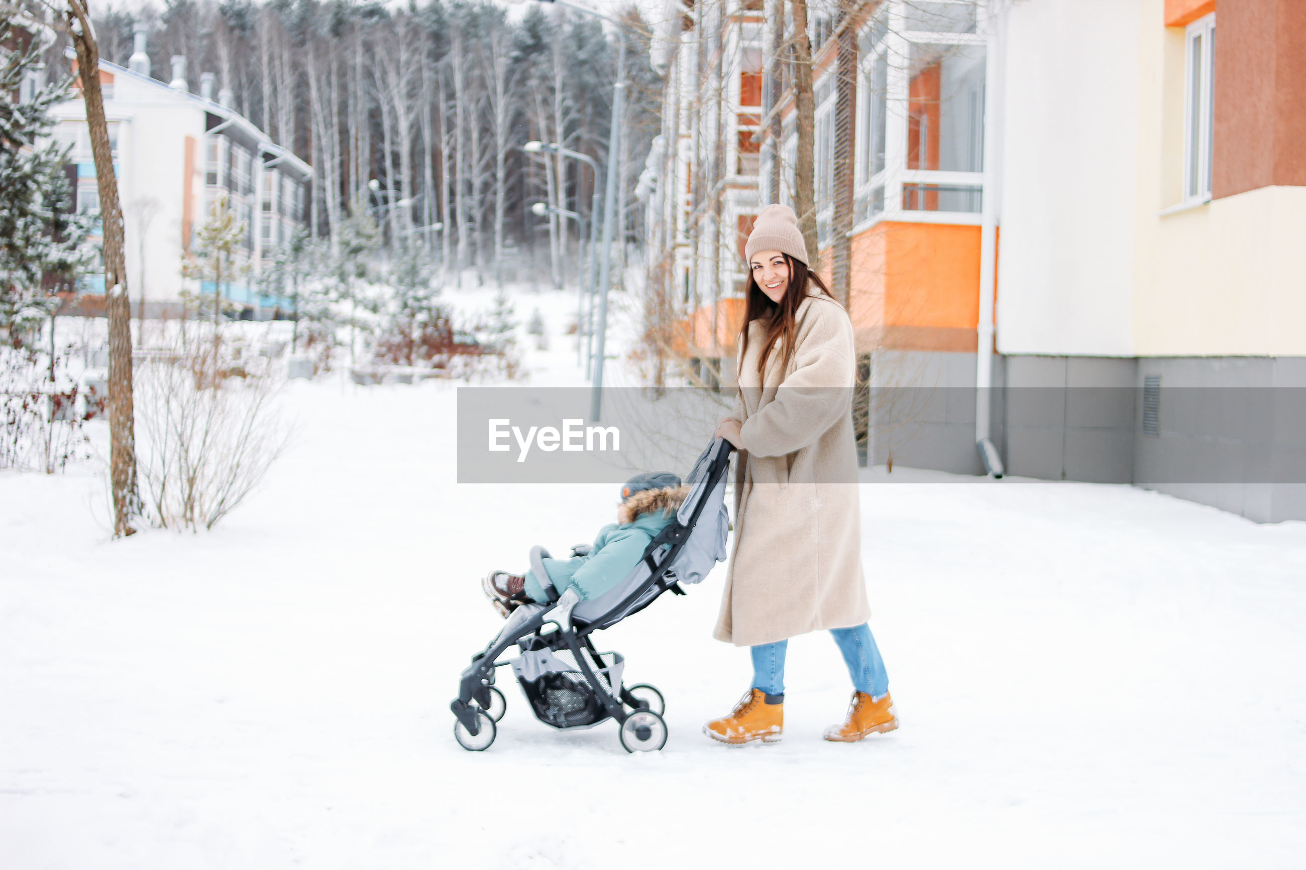 WOMAN WITH UMBRELLA WALKING ON SNOW COVERED BUILDINGS