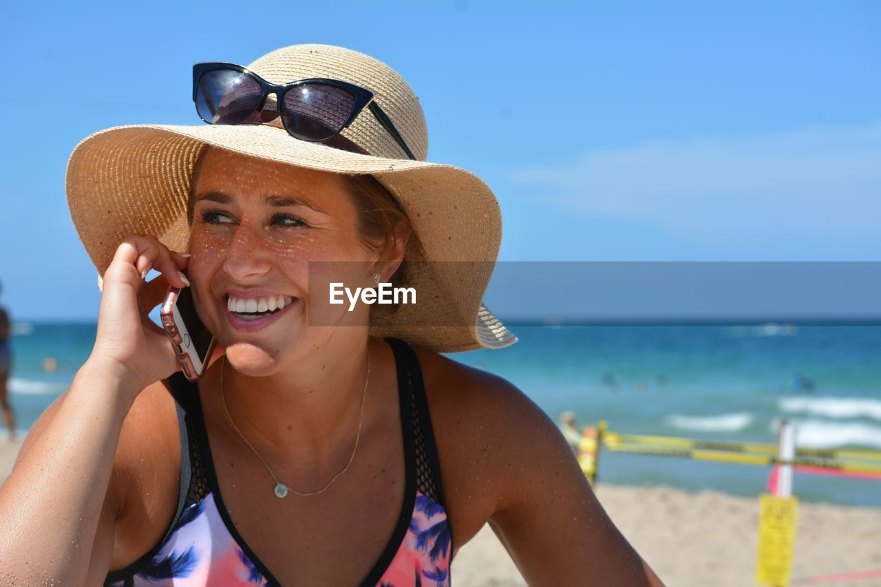 Smiling young woman talking on mobile phone at beach
