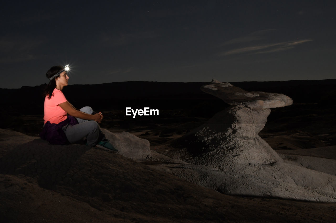 Side View Of Woman With Illuminated Headlamp Sitting At Desert During Night