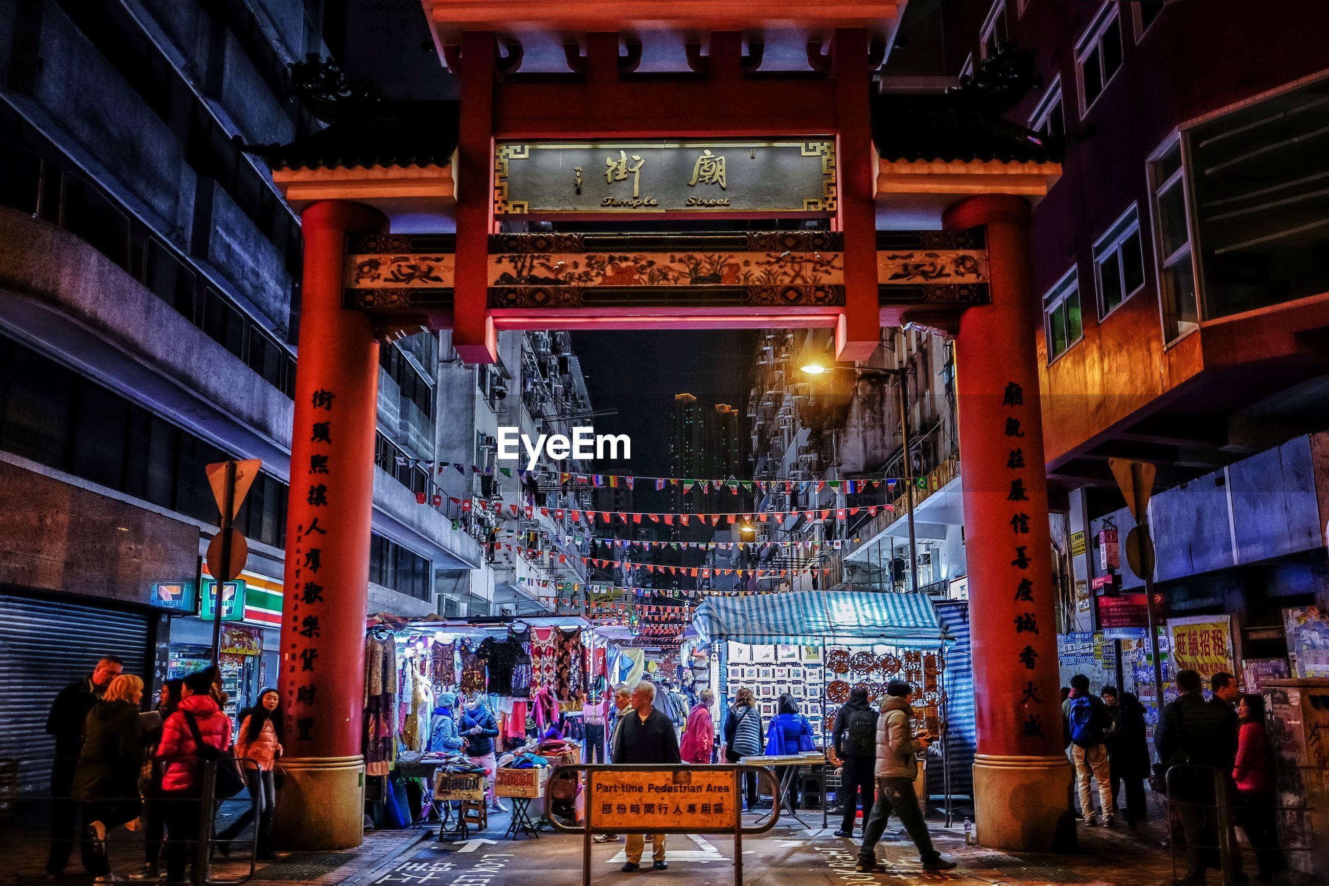 People at illuminated city street with torii gate