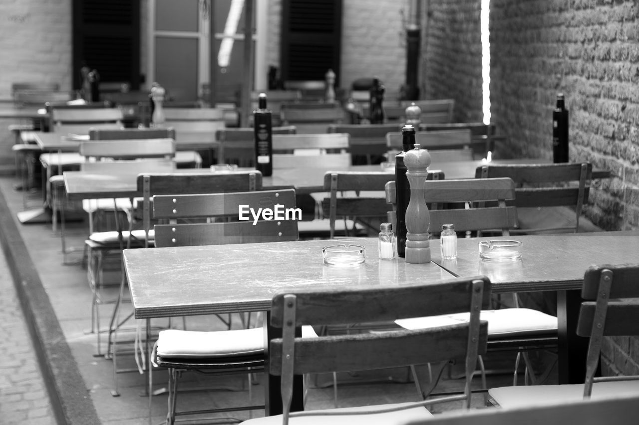 Empty Chairs And Tables Arranged At Restaurant