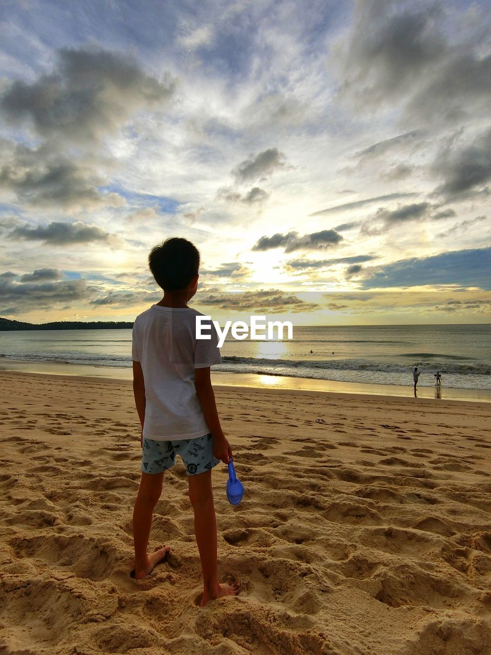 Rear view of boy standing at beach against cloudy sky during sunset