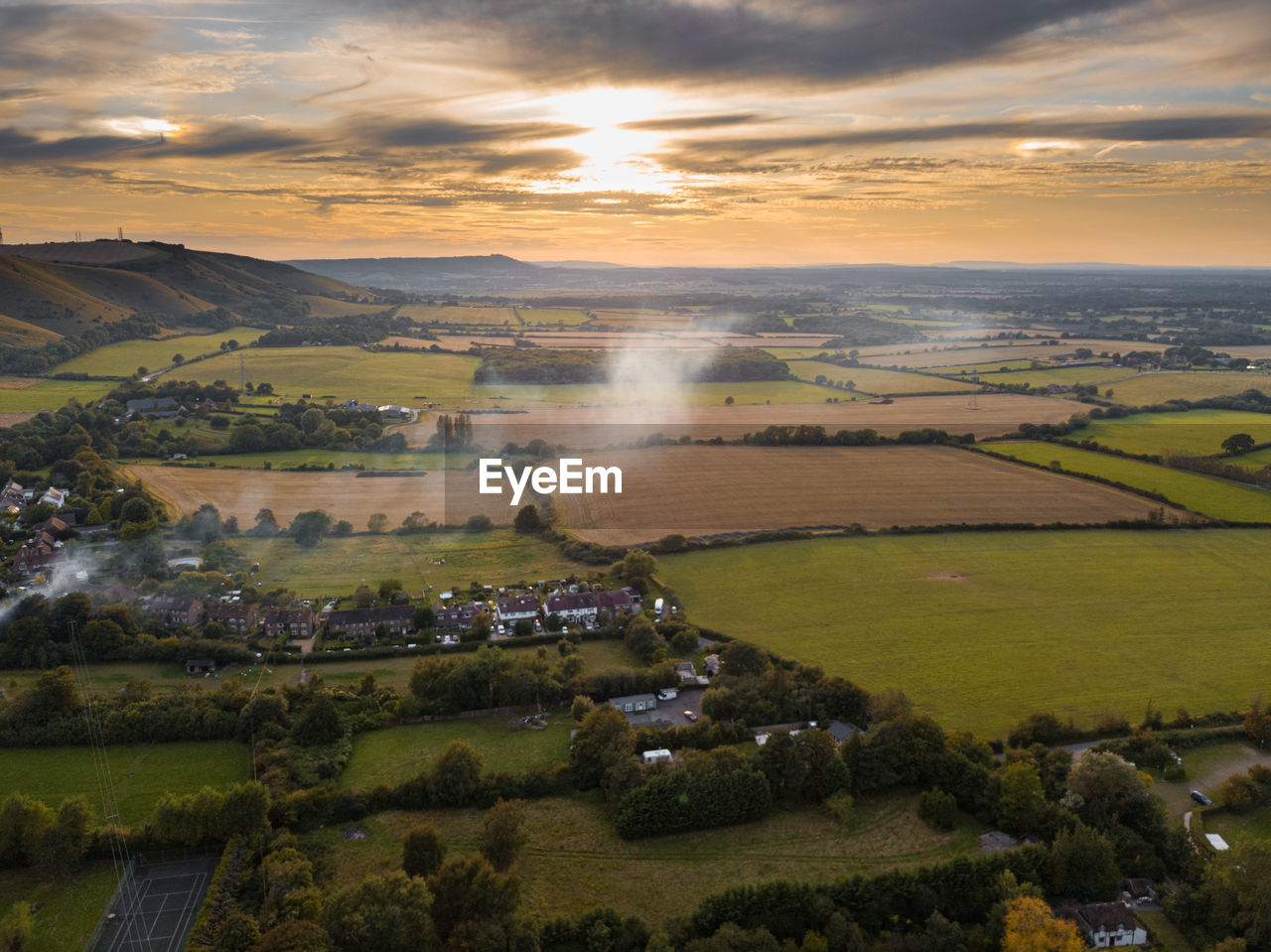 AERIAL VIEW OF AGRICULTURAL LANDSCAPE AGAINST SKY DURING SUNSET