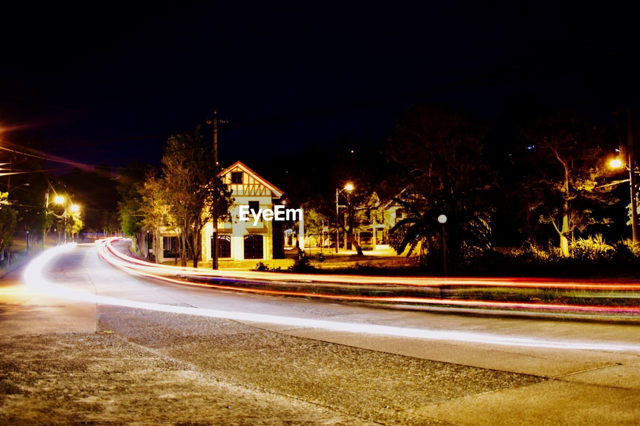 LIGHT TRAILS ON ROAD ALONG BUILDINGS