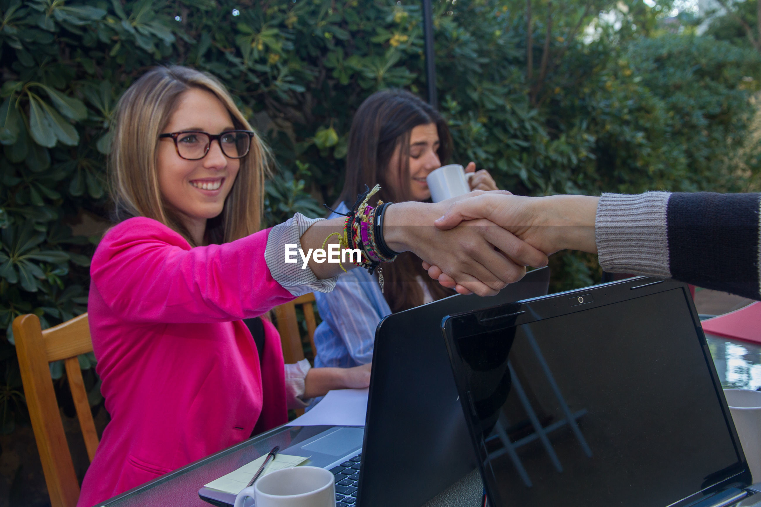 Businesswomen shaking hands with colleague against plants