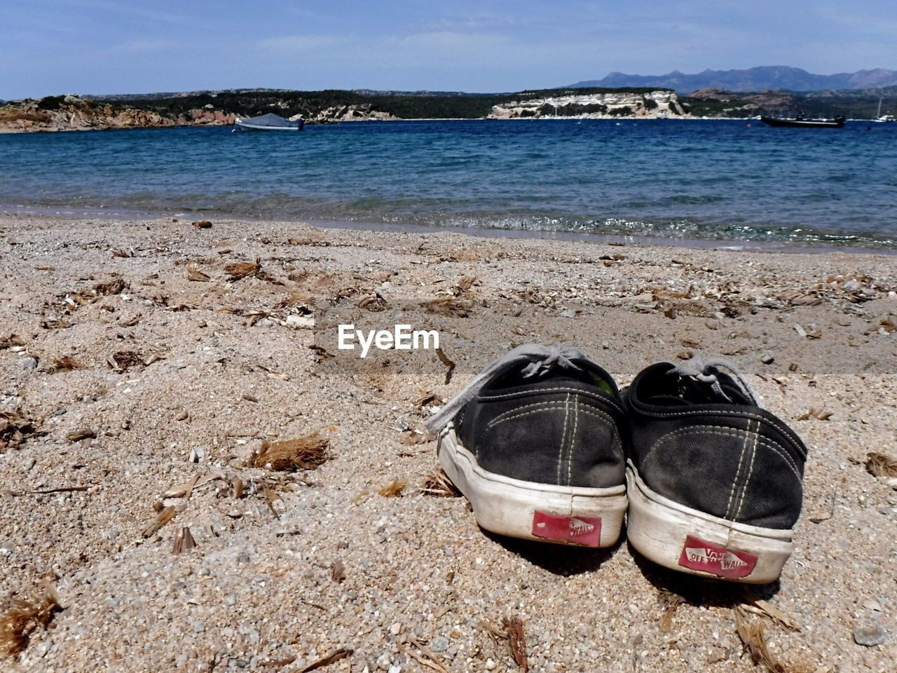 HIGH ANGLE VIEW OF SHOES ON SAND AT BEACH