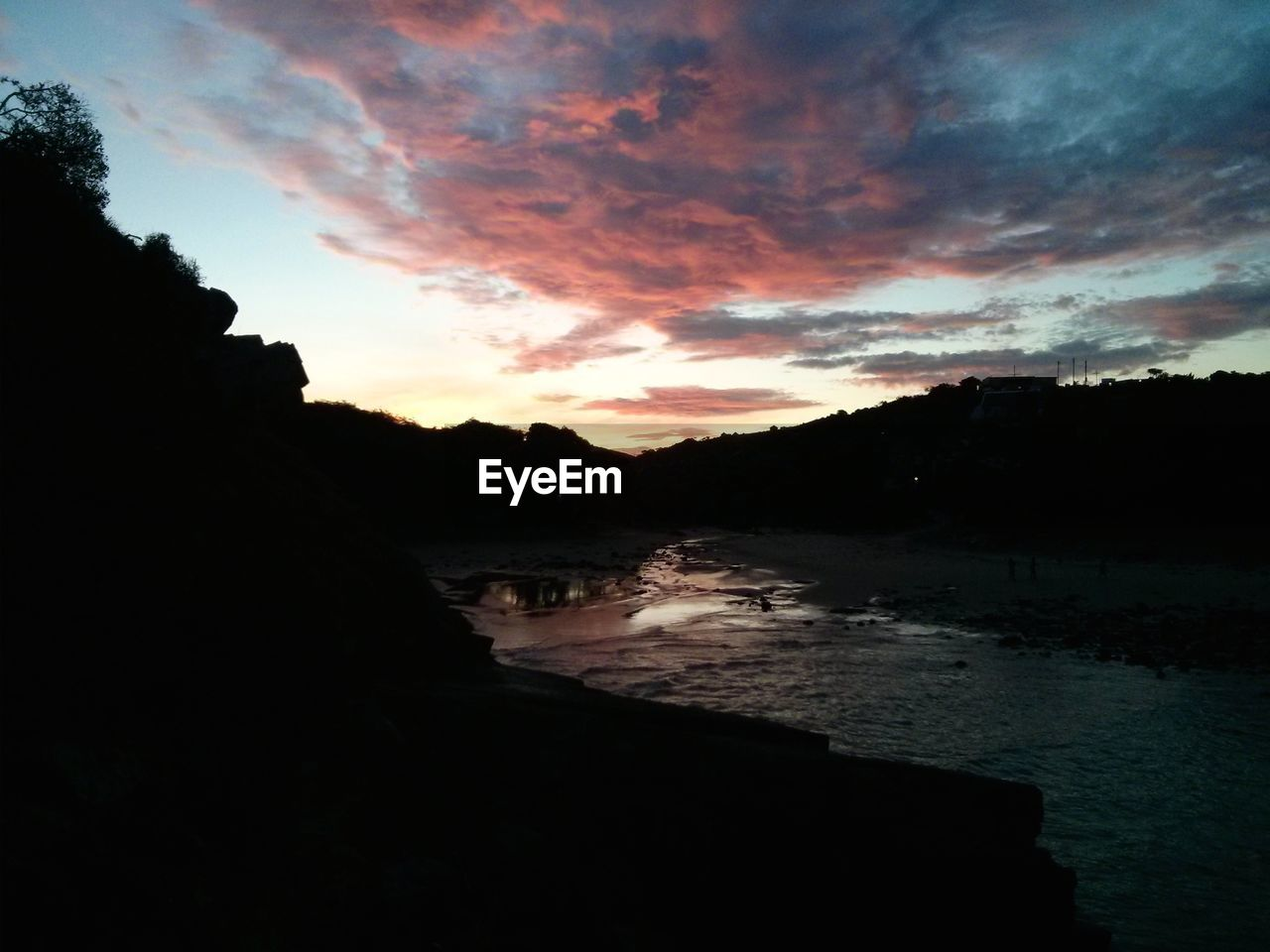 River Amidst Silhouette Mountains Against Cloudy Sky During Sunset