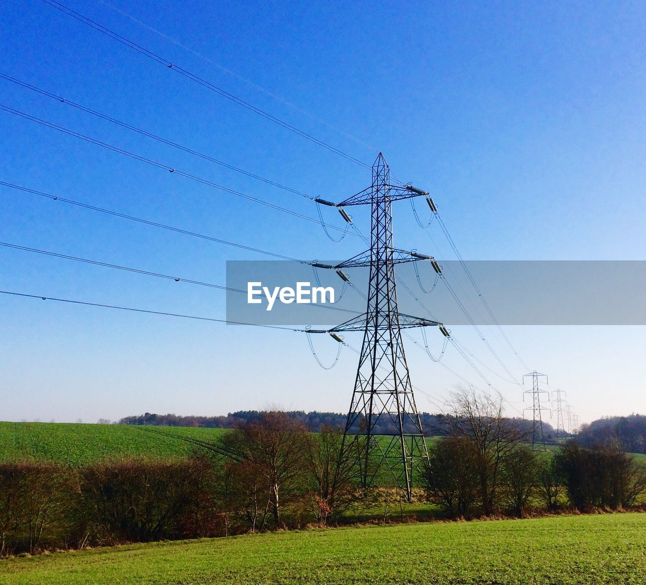 cable, electricity, connection, electricity pylon, power supply, fuel and power generation, power line, grass, field, no people, day, outdoors, landscape, nature, tranquility, clear sky, tree, low angle view, technology, sky, beauty in nature