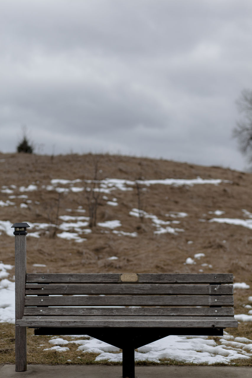 Empty bench against field during winter